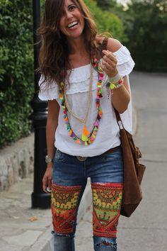 pantalon avec des imprimés amérindiens, chemisier blanc épaules nues, sac ample en nubuk, comme les sandales ou les bottines. Grand collier en plumes, ou autre breloques