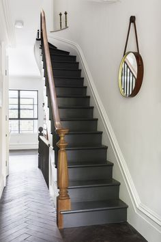 Reclaimed oak with a custom finish by LV Wood surrounds a staircase in a herringbone pattern. The new stairs are painted off black by Farrow & Ball, and the handrail that lines them is of salvaged mahogany.