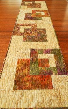 This modern batik table runner features four beautiful batik prints in shades of purple, green, gold, and orange with leaf motifs and two creamy gold background prints. It would be a pretty addition to your fall decor, but could also be used year round.  The size is approximately 14 X 55 (36 X 140 cm) - a versatile size for use on a dining table, buffet, coffee table or a bedroom dresser.  I machine-quilted a flowing meander in light brown thread. On the back I used another batik print with…