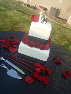 Black and red two tier cake with roses
