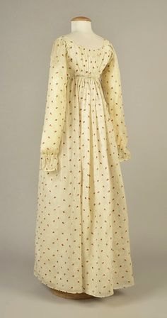 LOT 91 MUSLIN DRESS with CREWEL EMBROIDERY, AMERICAN, 1810 White cotton embroidered with pink, red and olive green posies, having fall-open bodice and long sleeve with slightly puffed cuff, front neckline edged in three ruched bands, bodice back and sides lined in cotton, center back gathered, narrow tie threaded through two loops at back. DLM tag. B-32, L 48-51.
