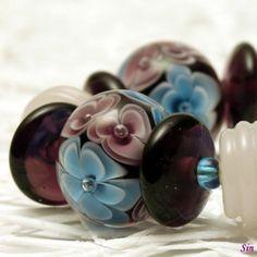 Náramek Fialka růžová Náramek obsahuječtyři kusy diskovitých květinových vinutek atřináct doplňkových korálků v zajímavé kombinacifialové, modré a růžové barvy. Délka náramku je21 cm, odpovídá obvodu zápěstí cca17 cm. Vinutky jsou navlečené na bižuterním lanku, zakončeno bižuterními komponenty.