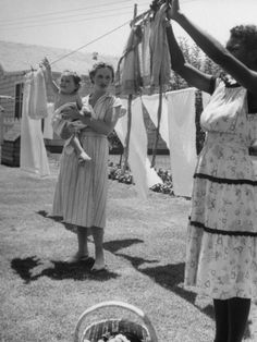 "What was in everyone's back yard? Clothes Lines for outdoor drying! We used to make ""people"" out of the straight wooden clothespins. Did you run around through the sheets too? I remember the big wicker clothes basket for carrying the wet laundry out and dried laundry in. Oh, and my mom in a housedress...!!!"