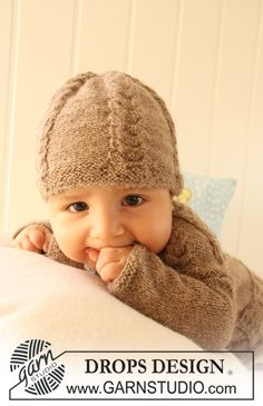 """Set comprises: Knitted DROPS jacket with raglan sleeves, hat and booties with cables in """"Alpaca""""."""