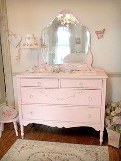 This antique dresser is from the 1930's and features an ornate mirror which comes off easily for transporting, newly added glass knobs, and four drawers. It has been refinished and painted a soft pink and distressed to enhance its shabby chic look. This piece would look great in any shabby cottage bedroom.
