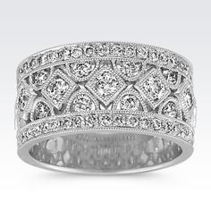 This divine ring is accented by 51 round diamonds, at approximately 1.40 carats total weight, pavé-set in quality 14 karat white gold. The diamonds are held in decorative designs of both squares and half-moons and are accompanied by milgrain detailing.