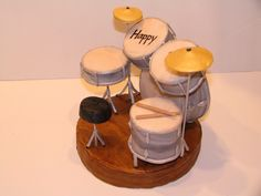 Drum Set - This is a cake topper for a boy who is turning 13.  He's the drummer in a band named Jester.  All the drums are rice krispy treats covered with marbled gumpaste made to look like his drum set and painted with luster dusts.  The stage is styrofoam covered with gumpaste.  I needed that so I'd have something to stick the stands for the stool, cymbals and some of the drums into.  I just made the topper; mom wanted to make her own cake.  This was a lot of fun to make!
