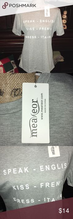 """Fun gray tee graphic with tie in back NWT SZ L Brand new with tags. Size large gray short sleeve tee with cute tie on back by neck with key hole opening. Front says speak English kiss French dress Italian. Fun graphic tee available in grey or blue see blue listing too. 50/50 poly/acrylic underarms across 21"""" shoulder to bottom 26"""" bottom edge across is 21-1/2""""  waist area across is 18-3/4"""" meaneor Tops Tees - Short Sleeve"""
