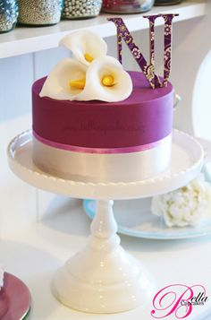 Gorgeous single-layer deep purple wedding cake with tonal purple and white ribbon trim at the base. Topped with edible white cala lillies and the purple-floral covered upright couple's initials N and J.