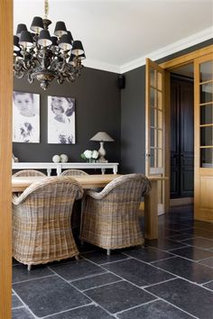 belgian bluestone flooring with charcoal gray walls, wicker kubu chairs and a rustic table, industrial look with warmth from wood in tall french doors, oil rubbed bronzed chandelier with black shades, family pictures in black and white on the wall, european mix
