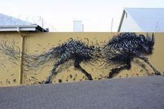 """El nuevo mural de Dal que se expande por casi dos cuadras en Windhoek, Namibia es titulado """"Breaking Tempo."""" Varias piezas con su estilo distintivo de animales hechos con listones, lucen corriendo, brincando y desasiéndose a lo largo del mural."""