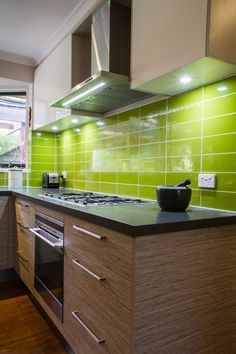 Green splashback. Contemporary kitchen. Exposed rangehood. www.thekitchendesigncentre.com.au