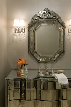 Elegant powder room features a traditional mirrored vanity with an undermount silver sink, finished with a crystal faucet, below a Venetian mirror flanked by crystal droplet sconces over taupe painted walls.
