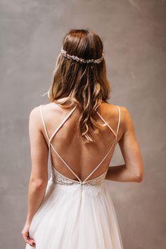 Chica con un vestido de novia con escote en la espalda posando para una sesión de fotos