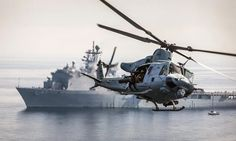 A UH-1N Huey with Marine Medium Helicopter Squadron, 15th Marine Expeditionary Unit (MEU), flies past the USS Rushmore