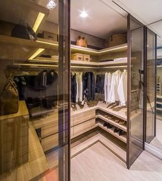 Closet Walk-in | Portas de correr em vidro bronze fecham o closet! Destaque para a iluminação embutida nas prateleiras! ✨ Projeto @claudiaalbertiniarquitetura | Foto @demian.golovaty