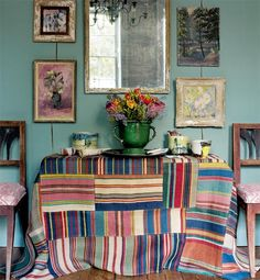 an unexpected patchwork of bright textiles and gently faded art against cool ocean blue-green walls; jug of flowers