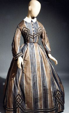 Day dress ca. 1862-64. Blue & brown plaid silk taffeta. High round neckline; whitework collar; blue silk-covered buttons down center front; hidden hook & eye closure at center front; dropped shoulder seam; narrow pagoda sleeves. Skirt has box pleats in front & cartridge pleats in back; brown ribbon appliquéd in geometric design across bodice, at sleeve hem, & along hem of skirt. de Young/Legion of Honor/Fine Arts Museums of San Francisco