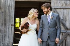 Family farm wedding with bride smiling at her groom while holding one of the family's chickens!