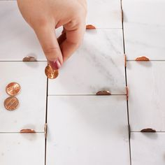 When setting tile, place pennies on end between the corners of each piece for spacers that are easy to remove. | Photo: Laura Moss | thisoldhouse.com
