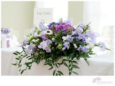 purple - low centerpiece so your guest can talk - keep the tall outstanding bouquets to the entrance, bar, escort table, dessert tables and the like