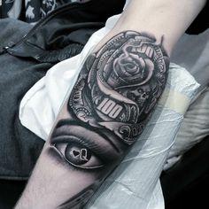 tatuajes en el antebrazo de ojo y rosa