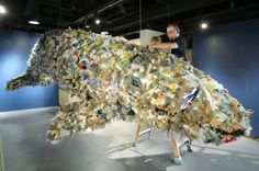 Olympic College art student Max Greene of Port Orchard places pieces of plastic bags on a life-size baby gray whale that is the centerpiece of The Whale Project exhibit at OC. LARRY STEAGALL / KITSAP SUN