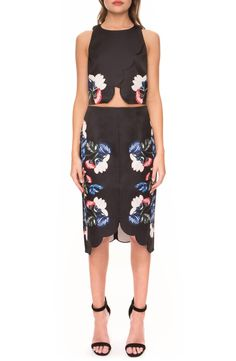 An abstract floral print enlivens the blackened background of a pretty midi-length skirt framed with a flattering high waist and scalloped hemline.