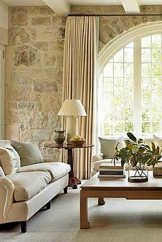 Interior design inspiration from a family room designed by Phoebe Howard with limestone wall, magnificent arched window, and white decor. - Interior design inspiration from a family room designed by Phoebe Howard with li. Living Room Remodel, Home Living Room, Living Room Designs, Living Room Decor, Stone Wall Living Room, Apartment Living, Living Area, Bedroom Decor, Interior Design Inspiration