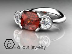 An 18kt Palladium White Gold ring with a Regal Cushion Cut Red Ruby and two Brilliant White Diamonds!