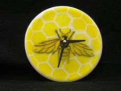 Round Honey Bee Clock, Bee Wall Clock, Honeycomb Clock, Round Wall Clock, Beekeeper Gift, Gift for Teacher, Kids Room,. This round honeycomb and bee clock is made in white glass, with yellow, orange and black frit (powdered glass) in a honeycomb pattern with a bee. The Clock measures 6.5 inch round and the mechanism is a Quartz Clock. It is hand-cut and than fused several times. All my creations are fired at temperatures up to about 1500 degrees and then annealed (slowly cooled) for…
