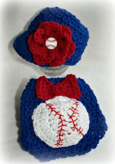 Take me out to the Ball Game!  Adorable Baby Girl Baseball Hat and Diaper Cover Set is a great way to show your favorite baseball/softball team on some sweet little girl.  Ideal for local White Caps, Big Teams like the Cubs, lil sister supporting her elementary brother's team, even church teams!    The baseball is stuffed to give a 3D effect and obviously the bow for the girly part as well as the flower with the baseball button on the cap.    Visit http://www.etsy.com/KnotNecessarilySew