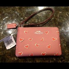 """Coach Heart Wristlet Gorgeous Heart Wristlet!  Red hearts adorn this mauve colored Coach wristlet.  Zip top closure with adjustable strap.  Fabric lined interior with 2 id slots. 6.25"""" x 4"""".  Comes with Coach gift box and gift bag. No Trades Coach Bags Clutches & Wristlets"""
