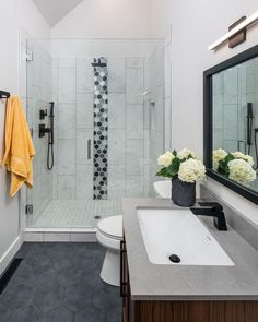 This bathroom's basic black, white and gray palette gets a dose of playful energy from a stripe of oversized mosaic tiles in the shower. Accessories add cheery color.