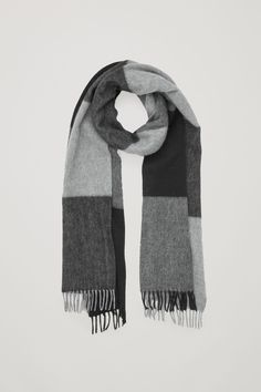 This scarf is made from a soft, lightly brushed wool-cashmere blend with a large checked pattern and flat twisted fringes at either end.