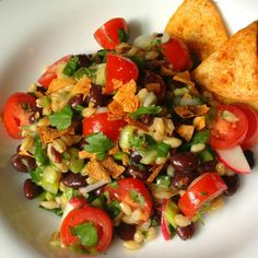 Black beans and barley are tossed with vegetables and sprinkled with baked corn tortilla chips in a lemon garlic vinaigrette to create a protein-packed meat less dish.