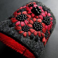Autorska bransoleta, szeroka, ozdobna, a lekka i wygodna. Wykonana ręcznie haftem płaskim i koralikowym . Bazę stanowi usztywniony trwały filc ( kolor antracyt). Bardzo wygodne zapięcie: koralik i podwójna pętelka z gumki. Wymiary: szerokość - ok. 6,3 cm, na nadgarstek 15-18 cm (można wyregulować przeszywając koralik). Polecam. Nietuzinkowy dodatek na każdą okazję.