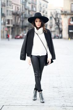Aida Domenech of Dulceida looking flawless in black leather pants, a chunky turtleneck sweater, high-heeled booties and adds detail with a cross-body bag, a wide-brimmed hat and a jacket draped over her shoulders