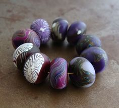 A set of 10 disk beads in spirals, floral and branch patterns in purple and berry colors, by HumbleBeads