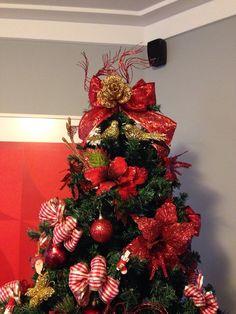 Arvore decorada com laços para presentes, flores e bolas, tudo com detalhes em vermelho - Castorina