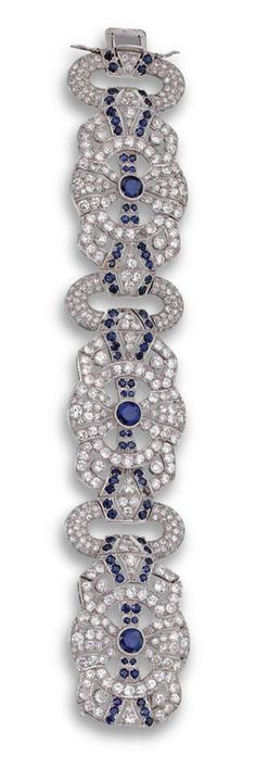 DIAMOND AND SAPPHIRE BRACELET, FRENCH, CIRCA 1930.  Designed as three articulated buckle motifs joined by open oval links, each set in the center with a round sapphire, set throughout with 413 round, old European-cut and single-cut diamonds weighing approximately 20.00 carats, further decorated with small round sapphires, mounted in platinum