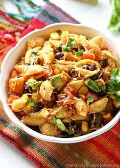 This Taco Pasta Salad is a cold Southwest pasta salad recipe filled with black beans, corn, cilantro, avocados, and tomatoes. It's tossed in a vinaigrette and sprinkled with cheese. the-girl-who-ate-everything.com