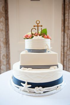 Nautical navy blue + white wedding cake idea - three-tier white-frosted wedding cake with starfish decor + sailor's knot with navy blue + white striped ribbon on each tier + gold initial cake topper with anchor {Pamela Price}