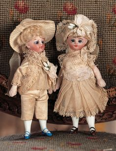 "Pair,German All-Bisque Dolls in Original Costumes  4"" (10 cm.) Each has bisque swivel head on bisque torso,cobalt blue glass inset eyes,painted lashes and brows,closed mouth,blonde mohair wig,peg- jointed bisque arms and legs,painted stockings,boy with blue shoes,girl with brown shoes. Condition: generally excellent. Comments: Germany,circa 1890. Value Points: in wonderfully preserved original matching costumes with bonnets and orange blossom decorations."