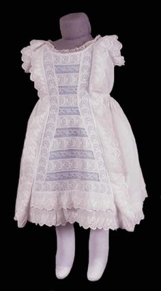 1885 Children's Dress - white cotton dress with low neck and short sleeves.  It has an elaborate apron front of lace and broiderie anglaise fitted back with full skirt, tucked above the hem.  Front, back of neck sleeves. and hem finished with broiderie anglaise frill.  Narrow lace edging at neck.