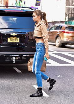 Gigi Hadid in skinny jeans, a cropped hoodie, and black booties.