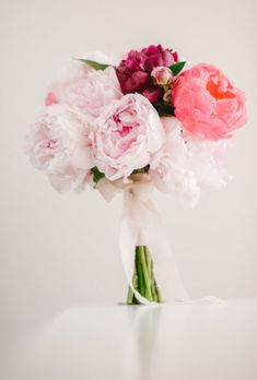 Brides.com: . Pale pink, coral, and burgundy peonies make up this stunning bouquet created by Australian florist Poppies Flowers.
