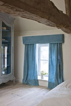 Old French linen bed sheets with an embroidered monogram made into curtains and dyed with Aubusson Chalk Paint, in Annie Sloan's Normandy house. From Colour Recipes by Annie Sloan published by Cico Books. Photo by Christopher Drake.