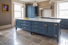 Stunning Guild Anderson kitchen painted in Little Greene Hicks Blue 208, handsomely adorned with Armac Martin bakes hardware in satin nickel. The walls are in Paint and Papers Moleskin 218 and marry perfectly with the Lucca limestone flooring by Ca'Pietra.  The contrasting Caesarstone White Attica worktops make the whole area light and fresh.  Appliances include the mighty Miele Mastercool fridge, a Steele Cucina range cooker and the all in one Quooker Fusion tap. Blue Kitchen Island, Kitchen Islands, Bungalow Renovation, Limestone Flooring, Little Greene, Range Cooker, Kitchen Paint, Lucca, Food Preparation