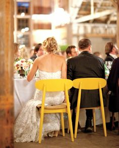 Instead of adorning chairbacks with swags, ribbons, signs, or other accoutrements, simply use a different color chair for the bride and groom. A simple and inexpensive touch.
